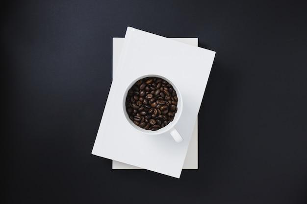 Kaffeebohnen in einer weißen kaffeetasse, die auf weiße bücher gesetzt wurde, stapelten auf einem schwarzen hintergrund Premium Fotos