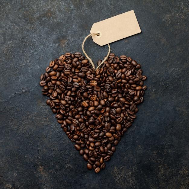 Kaffeebohnen in form des herzens auf dunklem rustikalem Premium Fotos