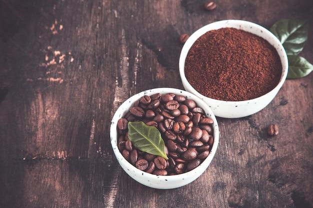Kaffeebohnen und gemahlener kaffee in den schüsseln mit kaffeebaum treiben auf einer dunkelheit blätter. Premium Fotos