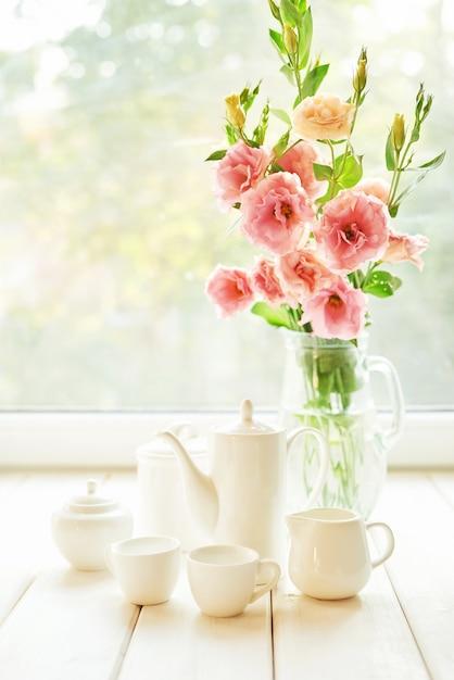 Kaffeegarnitur neben einer blumenvase auf einem tisch vor einem fenster Premium Fotos