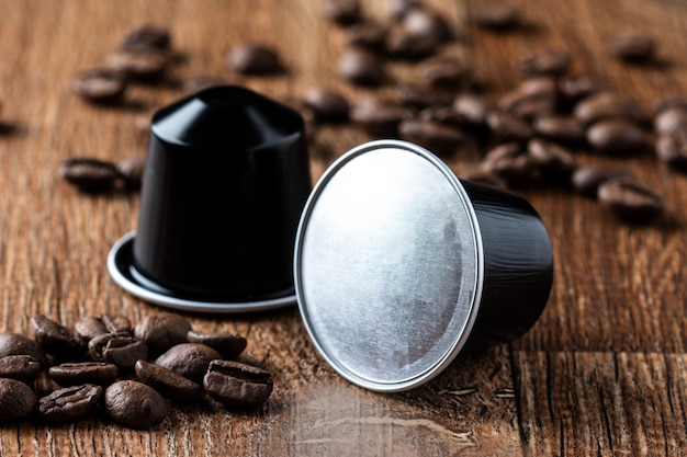 Kaffeehülsen auf holztisch oder capsula de cafe em madeira Premium Fotos