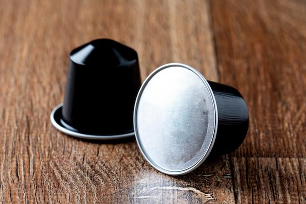 Kaffeehülsen auf holztisch oder capsula de cafe Premium Fotos