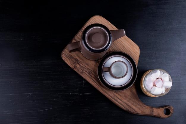 Kaffeekessel mit einer tasse und marshmallows auf einer holzplatte auf einem schwarzen. Kostenlose Fotos