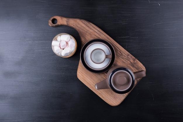 Kaffeekessel mit einer tasse und marshmallows auf einer holzplatte, draufsicht. Kostenlose Fotos