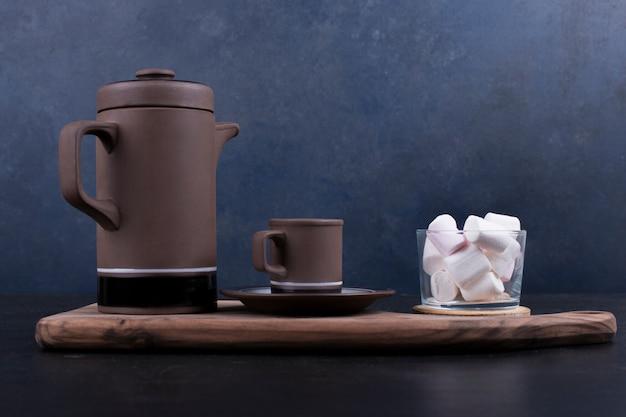 Kaffeekessel mit einer tasse und marshmallows auf einer holzplatte, profilansicht. Kostenlose Fotos