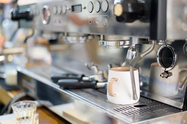 Kaffeemaschine macht schwarzen kaffee und gießt in eine tasse im café Premium Fotos