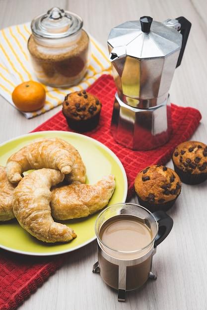 Kaffeemaschine, muffins, croissant, mandarine und eine tasse kaffee Premium Fotos