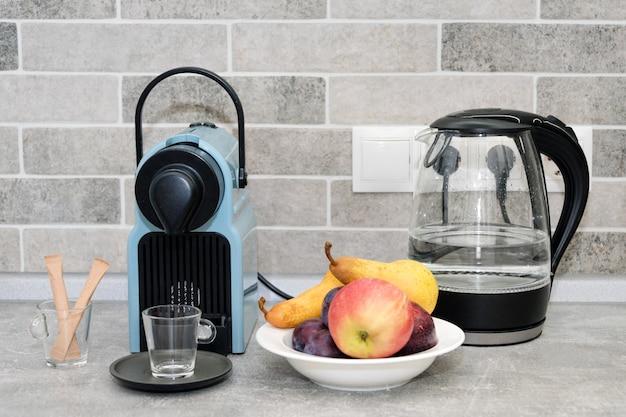 Kaffeemaschine und wasserkocher in der küche. frisches obst in weißer platte. Premium Fotos