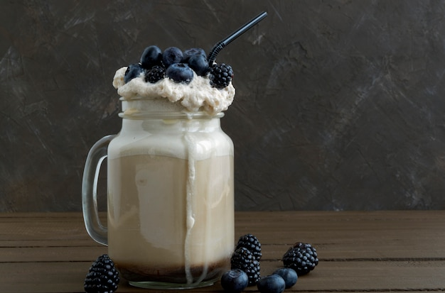 Kaffeemilchshake mit frischen beeren auf hölzernem hintergrund. Premium Fotos