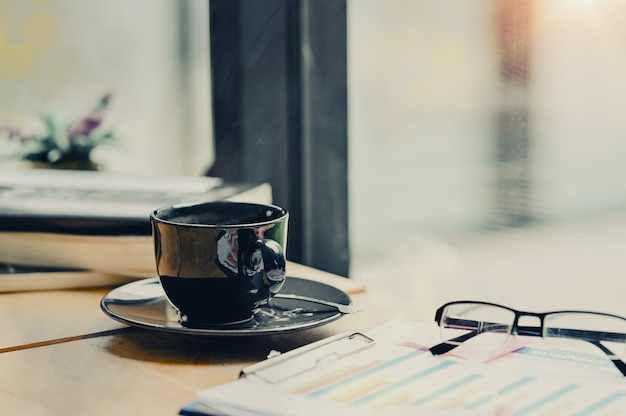Kaffeemorgenweinlesetonfoto, kaffeetasse auf geschäftsschreibtisch. Premium Fotos