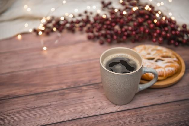 Kaffeetasse auf hölzernem hintergrund, appetitanregendem brötchen und weihnachtslichtern, selektiver fokus. Premium Fotos