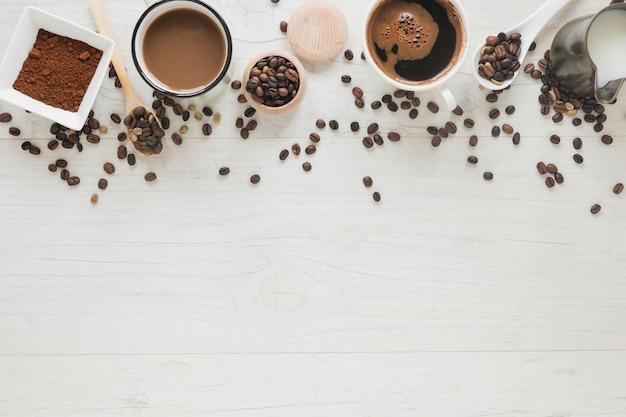 Kaffeetasse; geröstete bohnen; rohe bohnen; kaffeepulver und milch auf weißem holztisch Kostenlose Fotos