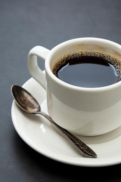Kaffeetasse hautnah. draufsichtlöffel und -platte des weißen tasse kaffees auf dunklem hintergrund Premium Fotos