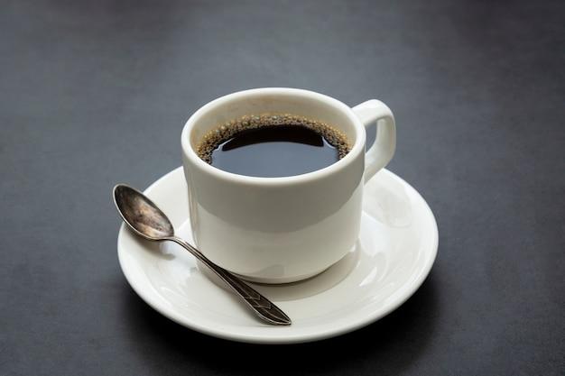 Kaffeetasse isoliert. draufsichtlöffel und -platte des weißen tasse kaffees auf dunklem hintergrund Premium Fotos