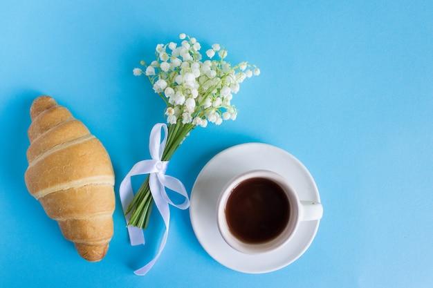 Kaffeetasse mit blumenstrauß des maiglöckchens und anmerkungen guten morgen, schönes frühstück, draufsicht, ebenenlage. croissant und kaffee Premium Fotos