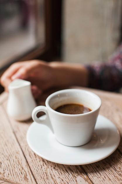 Kaffeetasse mit der defocus frauenhand, die milchkrug im cafã © hält Kostenlose Fotos