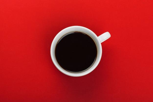 Kaffeetasse mit kaffeebohnen auf rot. Premium Fotos
