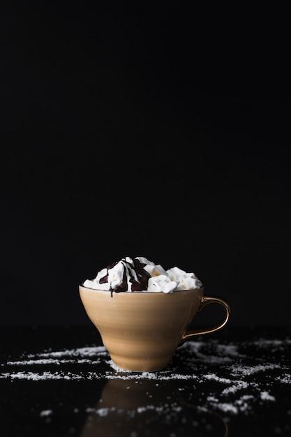 Kaffeetasse mit schlagsahne und schokoladensirup auf schwarzem hintergrund Kostenlose Fotos