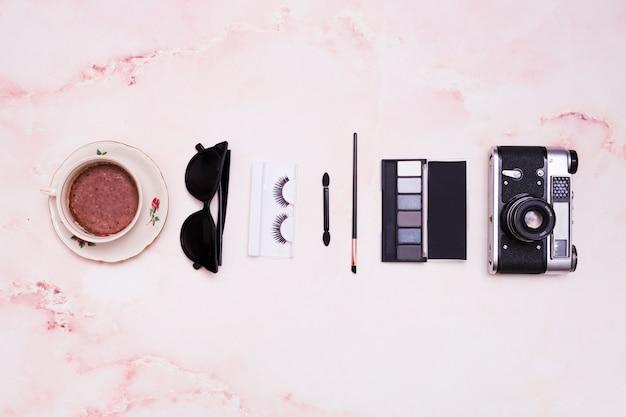 Kaffeetasse; sonnenbrille; wimpern; make-up pinsel; lidschatten-palette und vintage-kamera auf rosa strukturierten hintergrund Kostenlose Fotos