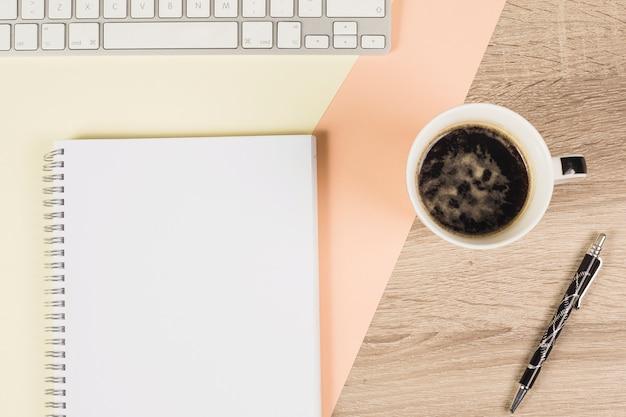 Kaffeetasse; stift; tastatur; und spiralblock auf farbigem und hölzernem hintergrund Kostenlose Fotos