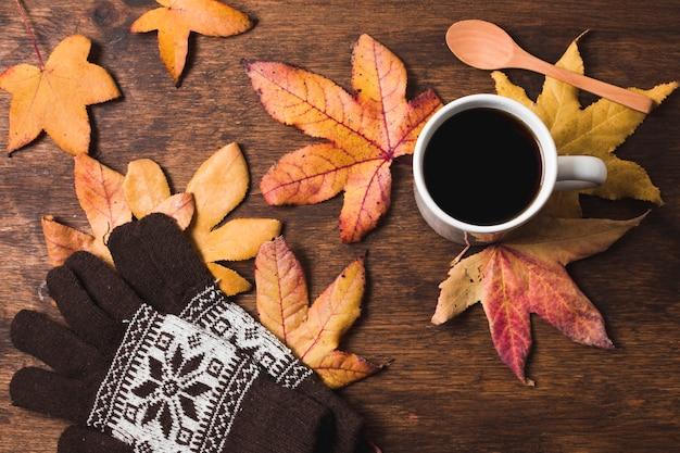 Kaffeetasse und handschuhe auf herbstlaubhintergrund Kostenlose Fotos