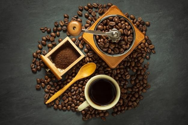 Kaffeetasse und kaffeeausrüstung auf schwarzem zementboden. Premium Fotos