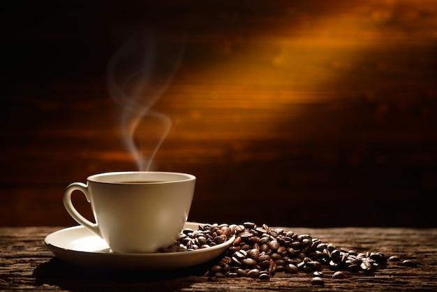 Kaffeetasse und kaffeebohnen auf altem hölzernem hintergrund Premium Fotos