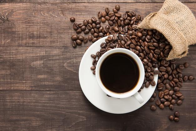 Kaffeetasse und kaffeebohnen auf holztisch. ansicht von oben. Premium Fotos