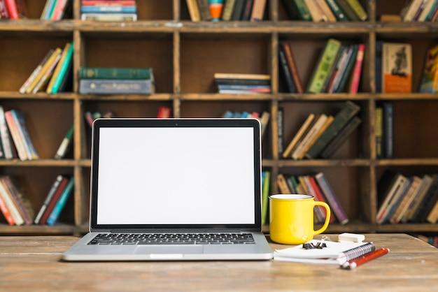 Kaffeetasse und laptop mit briefpapier auf hölzernem schreibtisch in der bibliothek Kostenlose Fotos