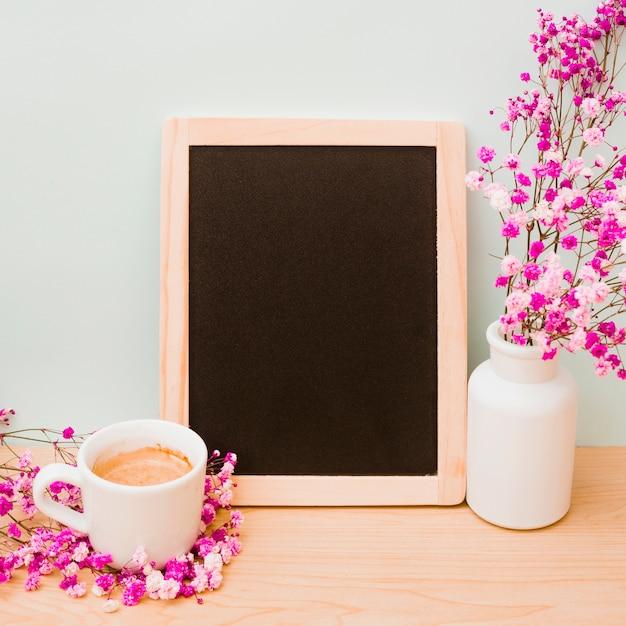Kaffeetasse und rosa vase des schätzchens des atems nahe dem leeren hölzernen schiefer auf schreibtisch gegen wand Kostenlose Fotos