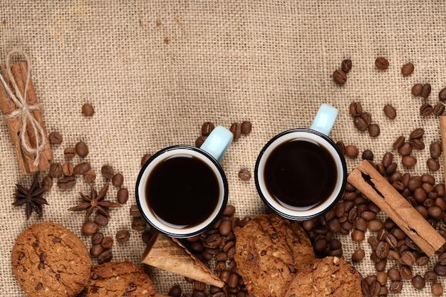 Kaffeetassen und bohnen, die mit plätzchen gestalten. Kostenlose Fotos