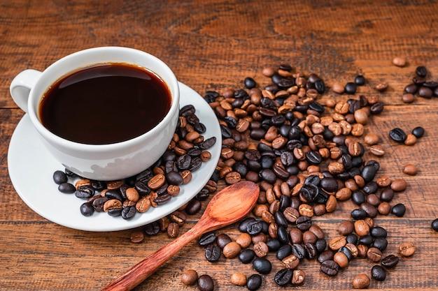 Kaffeetassen und kaffeebohnen auf einem holztisch Premium Fotos