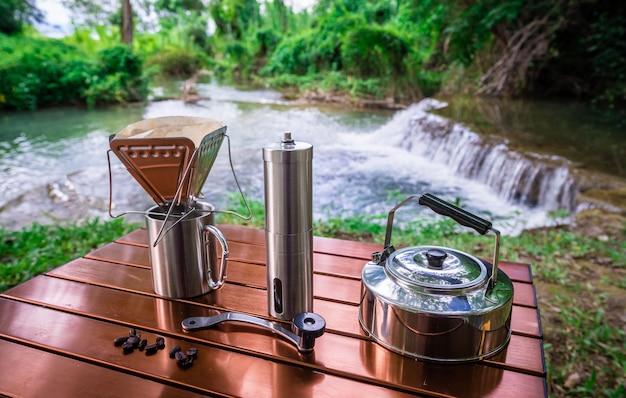 Kaffeetropfen beim kampieren nahe dem wasserfall Premium Fotos