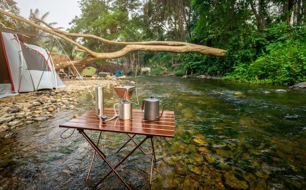 Kaffeetropfen beim zelten in der nähe des flusses im naturpark Premium Fotos