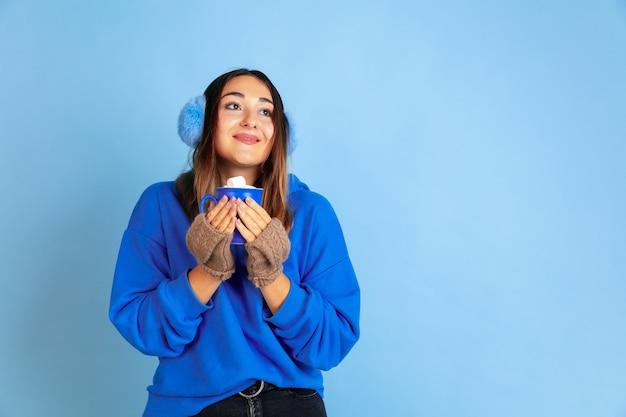 Kaffeezeit. porträt der kaukasischen frau auf blauem studiohintergrund. schönes weibliches modell in warmer kleidung. konzept der emotionen, gesichtsausdruck, verkauf, anzeige. winterstimmung, weihnachtszeit, feiertage. Kostenlose Fotos