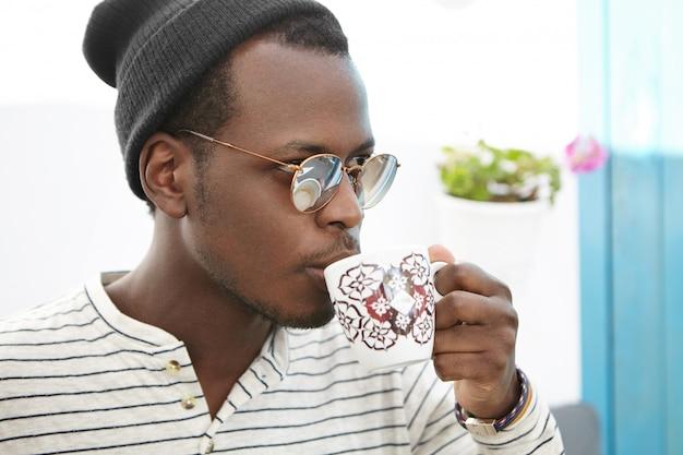 Kaffeezeit. selbstbewusster modischer afrikanischer mann in hut und schatten, der tasse hält, frischen cappuccino trinkt, mit nachdenklichem ausdruck vor ihm schaut und heißes getränk während des mittagessens im café genießt Kostenlose Fotos