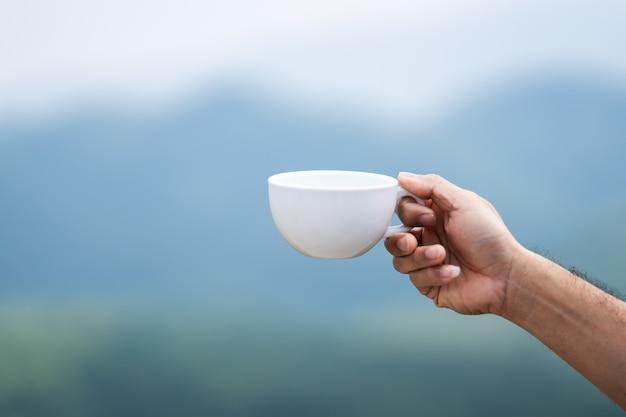 Kaffernaturkonzept, kaffeetasse an hand, die natur des nebels auf berg und himmel anhält Premium Fotos