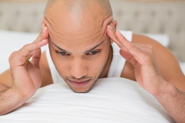 Kahler mann, der unter kopfschmerzen im bett leidet Premium Fotos