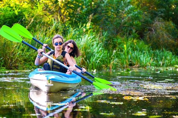 Kajakfahren mit der familie, mutter und tochter, die im kajak auf der flusskanutour spaß haben paddeln Premium Fotos