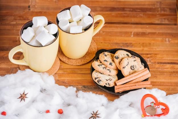 Kakaobecher mit marshmallows und teller mit keksen Kostenlose Fotos