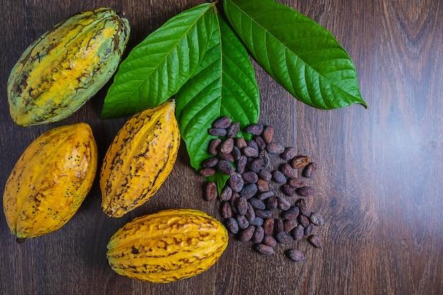 Kakaofrucht und kakaobohnen auf einem hölzernen hintergrund Premium Fotos