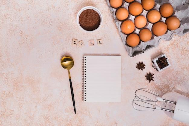 Kakaopulver; sternanis; kelle; spiralblock und elektrisches schneebesen mit kuchenblöcken auf strukturiertem hintergrund Kostenlose Fotos