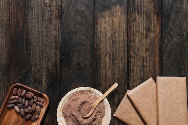 Kakaopulver und bohnen mit eingewickeltem schokoriegel auf holztisch Kostenlose Fotos