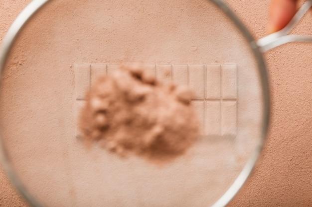 Kakaopulver wischte vom sieb auf schokoriegel ab Kostenlose Fotos