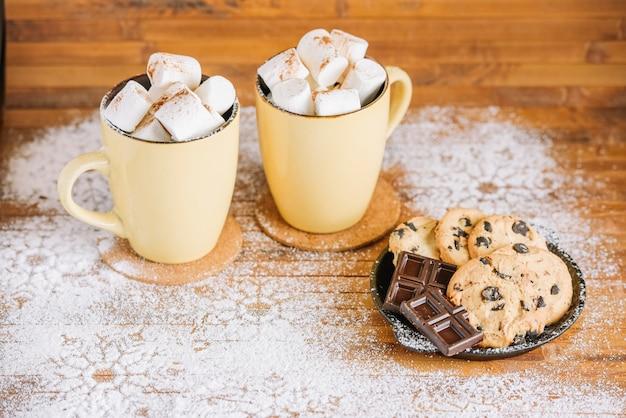 Kakaoschalen mit süßigkeiten auf tabelle Kostenlose Fotos