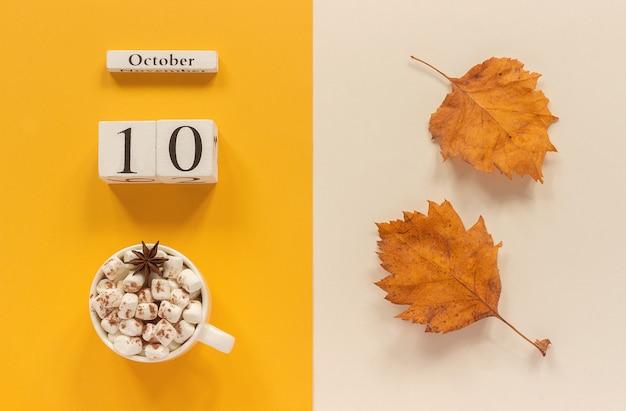 Kalender 10. oktober tasse kakao mit marshmallows und gelbem herbstlaub Premium Fotos