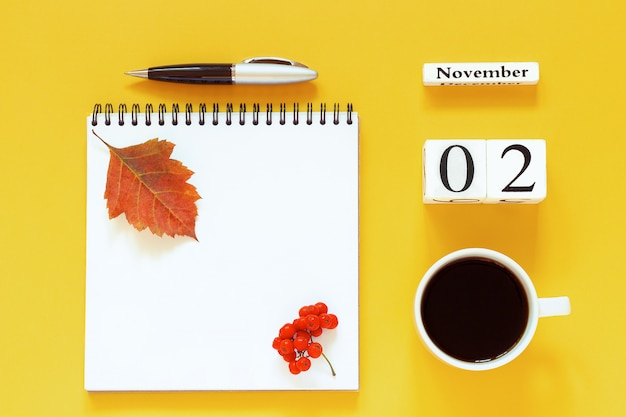 Kalender 2. november tasse kaffee, notizblock mit stift und gelbes blatt auf gelb Premium Fotos