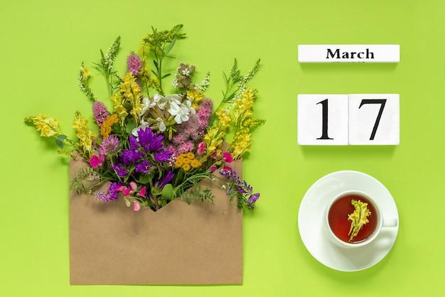 Kalender der holzwürfel vom 17. märz. tasse kräutertee, kraftumschlag mit bunten blumen auf grünem hintergrund Premium Fotos