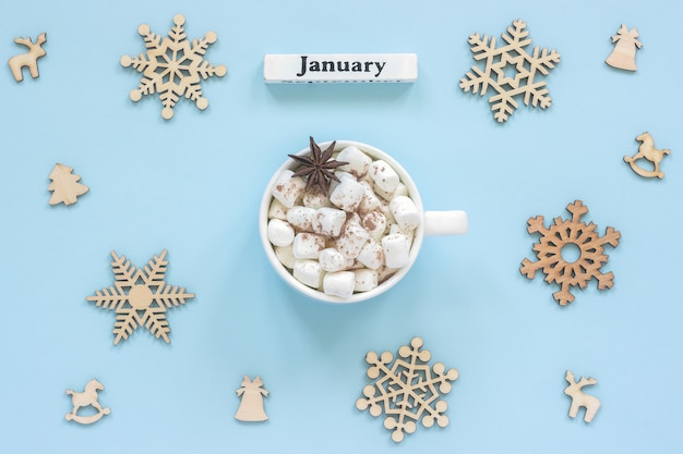 Kalender januar mug kakaomarshmallows und große hölzerne schneeflocken Premium Fotos