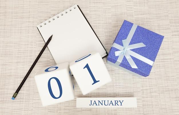 Kalender mit trendigen blauen text und zahlen für den 1. januar und ein geschenk in einer box Premium Fotos